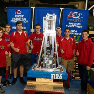 Students from team 1126 standing behind their robot.