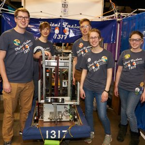 Students from team 1317 standing around their robot