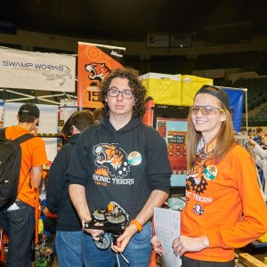 A student from team 1592 holds a part from their robot