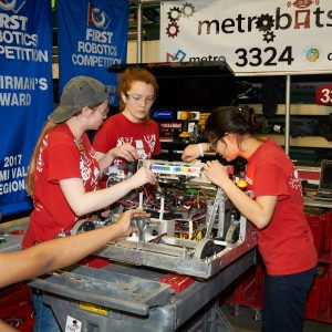 2018 - Students from team 3324 working on their robot in the pit area.
