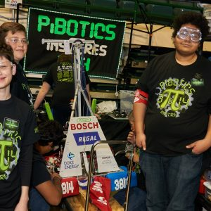 Students from team 3814 standing around their robot.