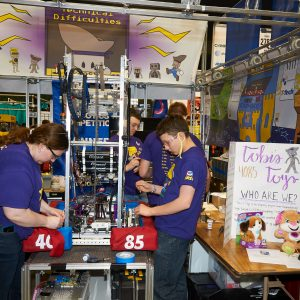 Students from team 4085 (Technical difficulties) working on their robot in the pit area.