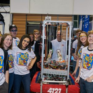 Students from team 4121 (Vikings) standing around their robot in the pit area posing for the camera.