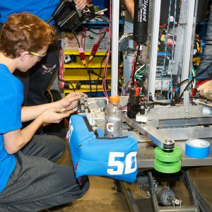 Students from team 5030 working on their robot in the pit area.