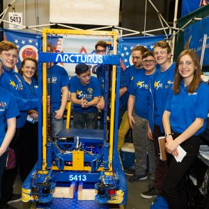The students from team 5413 (Stellar Robotics) standing in back of their robot in the pit area.