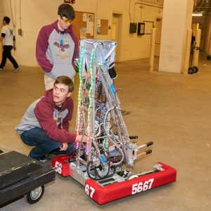 Students from team 5667 working on their robot near the practice field.