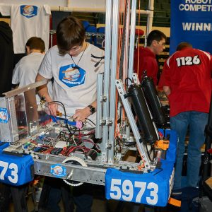 Students from team 5973 (Moonshots) working on their robot in the pit area.