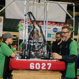 Students and mentors from team 6027 working on their robot in the pit area.
