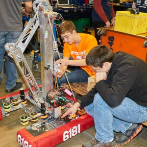 Students from team 6181 working on their robot in the pit area.