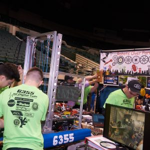 Another picture of team 6355 (Robots over Parma) working on their robot in the pit area.