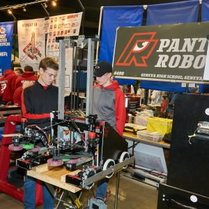 Students from team 6490 working on their robot in the pit area.