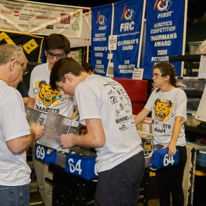 Students and mentors from team 6964 working on their robot in the pit area.