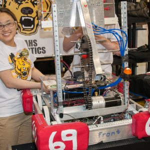 A student from team 6964 works on her team's robot.