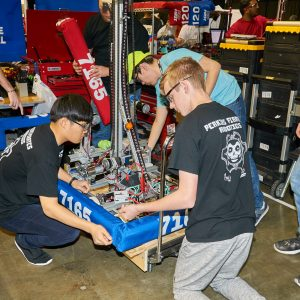 Students from team 7165 working on their robot in the pit area.