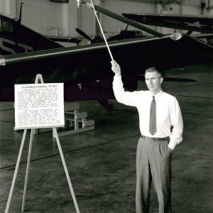 Man with pointer beside aircraft.