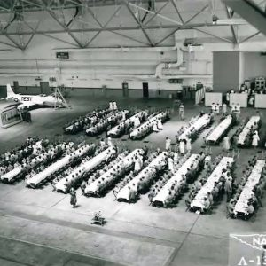 Group eating at banquet tables in hangar.