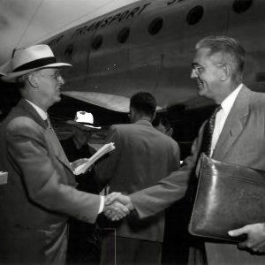 Men shake hands on tarmac.