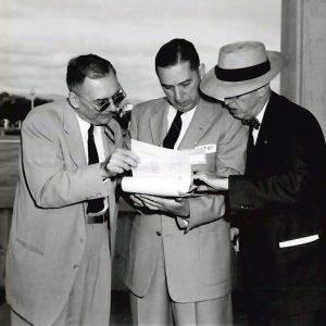 Three men examining document.