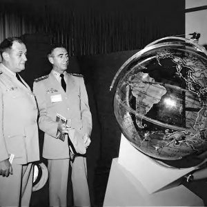 Two men examine globe.