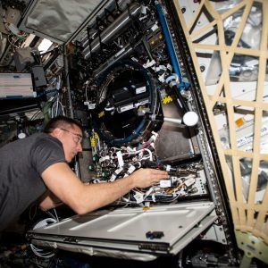 NASA astronaut Chris Cassidy works on the Combustion Integrated Rack, a device that enables safe fuel, flame and soot studies in microgravity.