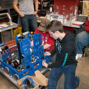 Students from team 3193 work on their robot in the pits area at the Buckeye Regional.