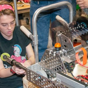 A student from all-girls team 2399 works on her team's robot in the pits area at the Buckeye Regional.