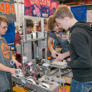 Students from team 3484 work on their team's robot in the pits area at the Buckeye Regional.