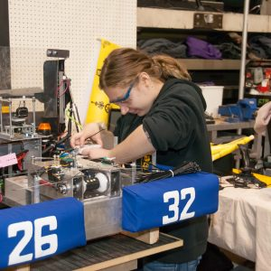 A student from team 2632 works on his team's robot in the pits area at the Buckeye Regional.