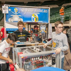 Students from team 4611 (O3Zone Robotics) work on their robot in the pits area at the Buckeye Regional.