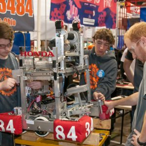 Students from team 3484 work on their robot in the pits area at the Buckeye Regional.