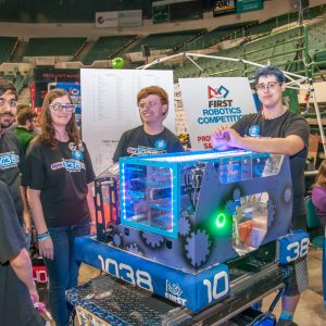 The high-tech bule glow from the LED lights on team 1038's robot can be seen as the students pose for the camera.
