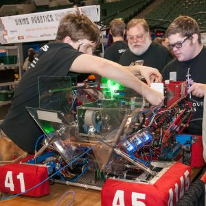 Several students and a mentor from team 4145 work on their team's robot in the pits area at the Buckeye Regional.
