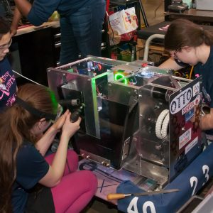 All girls from team 2340 work on their team's robot in the pits area at the buckeye Regional.