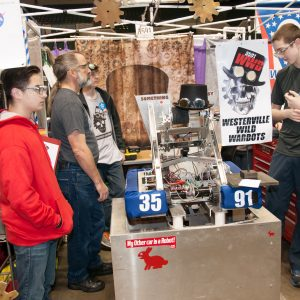 Students from team 3591 standing by their robot in the pits area at the Buckeye Regional.