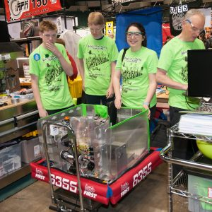 Students fromn team 6355 work on their team's robot in the pits area at the Buckeye Regional.