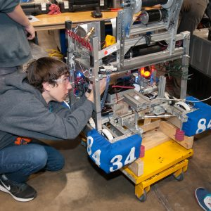 A student from team 3484 works on his team's robot in the pits area at the Buckeye Regional.