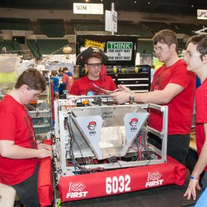 Students from team 6032 work on their robot in the pits area at the Buckeye Regional.