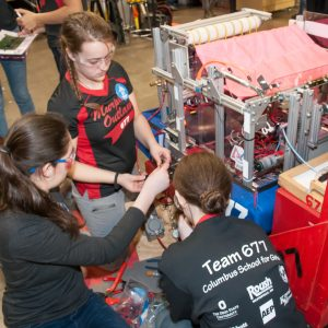 Students from team 677 (Columbus school for girls) work on their team's robot in the pits area at the Buckeye Regional.