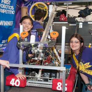 Several students from team 4085 pose for a picture with their robot in the pits area at the 2019 Buckeye Regional Robotics Competition.