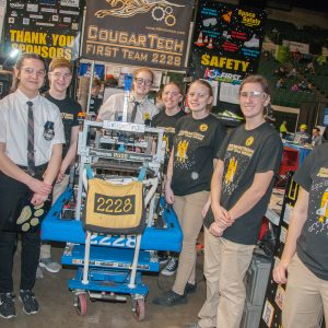The studentsd on team 2228 pose for a picture wigth their robot in the pits area at the 2019 Buckeye Regionl Robotics Competition.