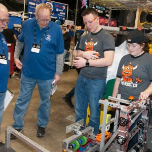 Several students from team 4121 talk to several judges ain the pits area at the 2019 Buckeye Regional Robotics Competition.