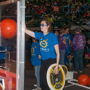 A team member prepares to deliver a payload (ball) and hatch cover to her team's robot.