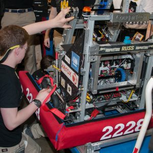 A student from team 2228 workx on her team's robot in the pits area at the 2019 Buckeye Regional Robotics Competition.