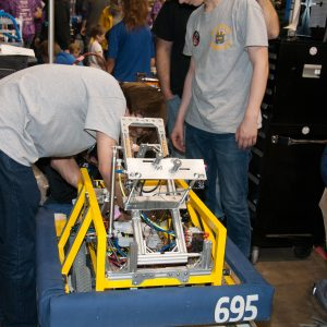 The students from team 695 work on their robot in the pits area at the 2019 Buckeye Regionl Robotics Competition.