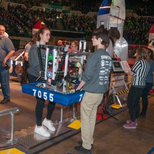 Several students from team 7055 carry their team's robot onto the playing field prior to the start of their match.