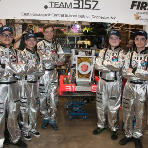 Several studenta from team 3157 dressed in their spacesuits pose for a picture with their team's robot.