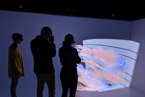 Three people with 3D glasses observe a 3D image of flames.