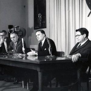 Men at table during press conference