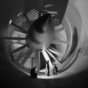 Two men in front of Altitude Wind Tunnel drive fan.