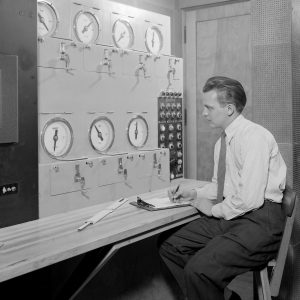 Researcher sits at Altitude Wind Tunnel Control Panel.